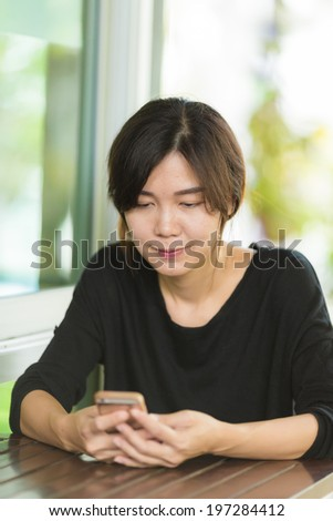 Woman using smart phone in coffee shop