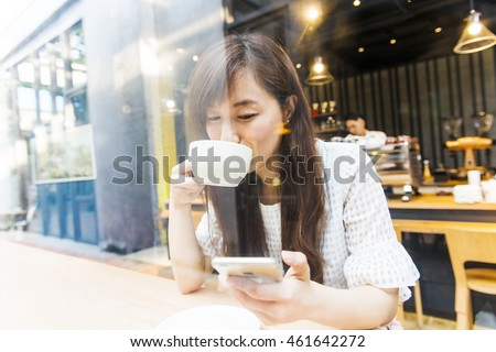 Woman using smart phone in the coffee shop