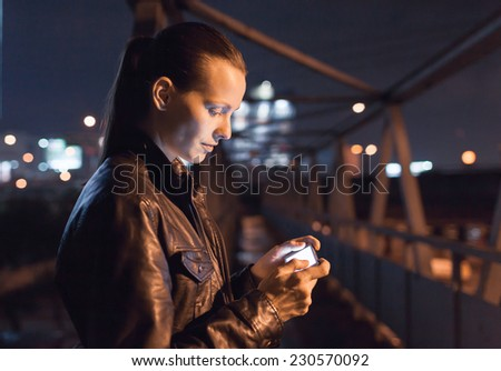 Woman using smart phone mobile in the city at night - stock photo