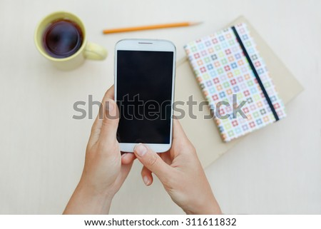 Woman using smart phone on the table. Phone with empty screen for your application - stock photo