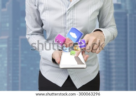 Woman using smart phone with finger touching screen and color app icons, front view, abstract blur background. - stock photo