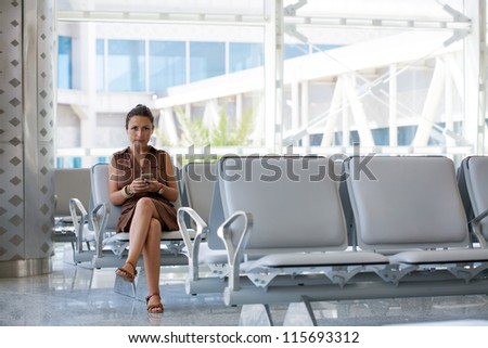 Woman Using Smartphone At Departure Lounge - stock photo