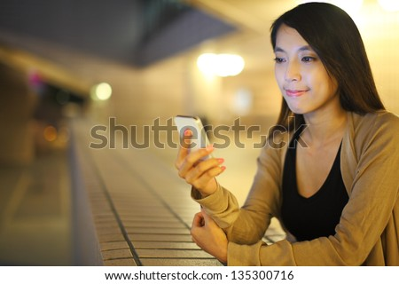 woman using smartphone in city at night - stock photo