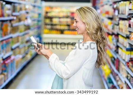 Woman using smartphone in supermarket - stock photo