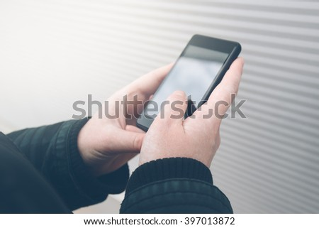 Woman using smartphone on the street, facing the wall while holding mobile phone, young adult female in urban surrounding texting sms or reading message, retro toned image, selective focus. - stock photo