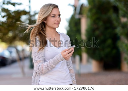 Woman using smartphone. Teen standing on a city street while holding a cell phone.