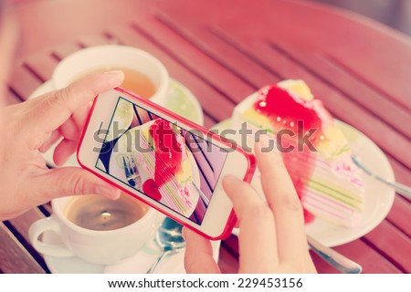 Woman using smartphones to take photos of food with instagram style filter  - stock photo
