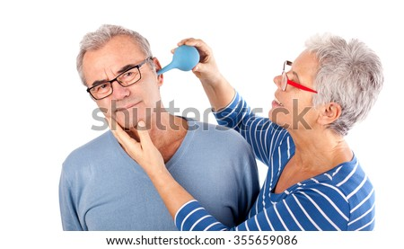 woman using soft bulb washer to clean the ear of her husband, health concept
