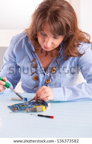 Woman using soldering tool for the computer parts.