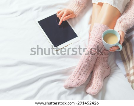 Woman using tablet at cozy home atmosphere on the bed. Young woman with cup of cocoa or coffee in hands enjoying free time with comfort. Soft light and comfy lifestyle concept. Technology in life. - stock photo