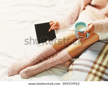Woman using tablet at cozy home atmosphere on the bed. Young woman with cup of milk in hands enjoying free time with comfort. Soft light and comfy lifestyle concept. Technology in life. - stock photo