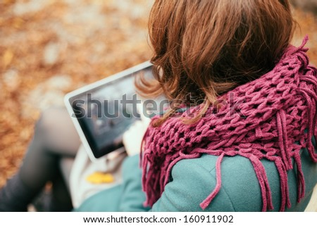 Woman using tablet computer outdoors - stock photo