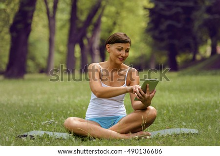 Woman using tablet on the grass. Smiling.