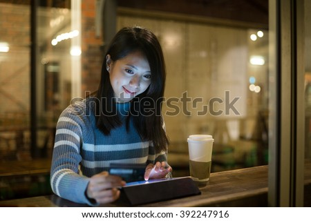 Young woman cafe drinking coffee using stock photo for Tablet hotel booking