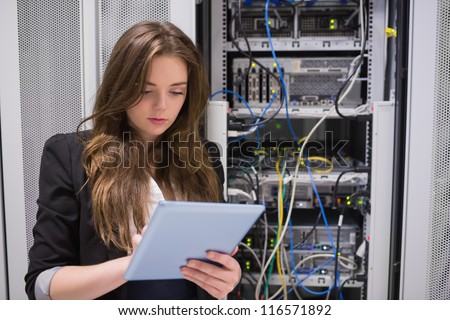 Woman using tablet pc in front of servers in data center - stock photo