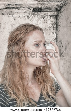 Woman using the asthma inhaler against image of a room corner - stock photo