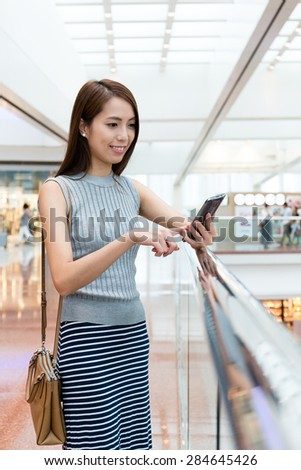 Woman using the mobile phone in shopping mall - stock photo