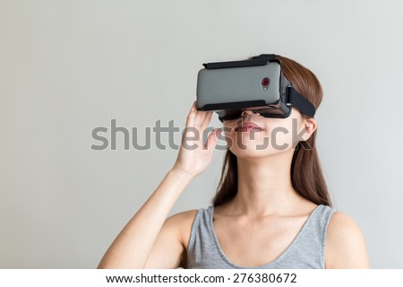 Woman using the virtual reality headset - stock photo