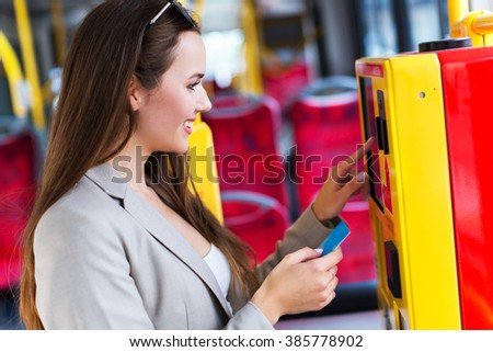 Woman using ticket machine on bus