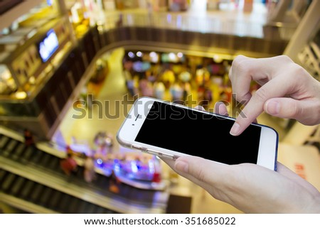 Woman using touch screen mobile phone with blur shopping mall - stock photo