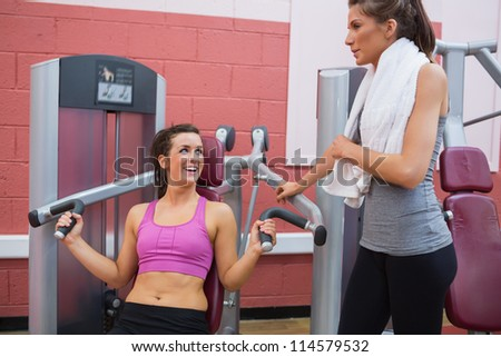 Woman using weights mahcine talking with friend in gym - stock photo