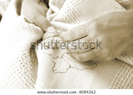 Woman using woolen yarn to embroider fabric - stock photo