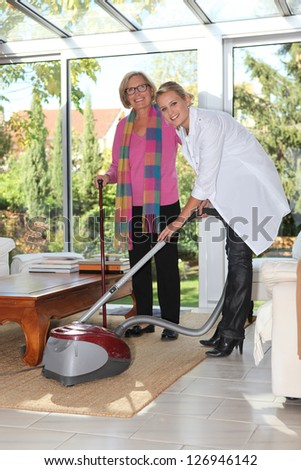Woman vacuuming for elderly lady - stock photo