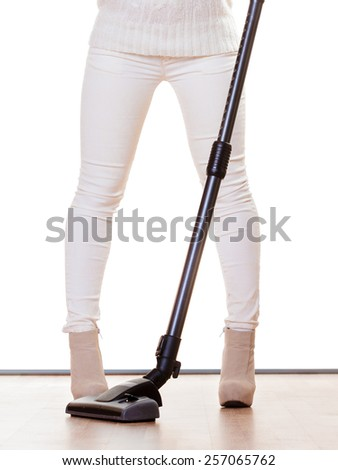 Woman vacuuming the house, female legs with vacuum cleaner. Housework