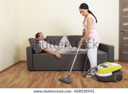 Woman vacuuming while man is resting on a couch
