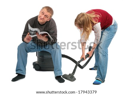 woman vacuums,  man sits on vacuum cleaner with magazine - stock photo