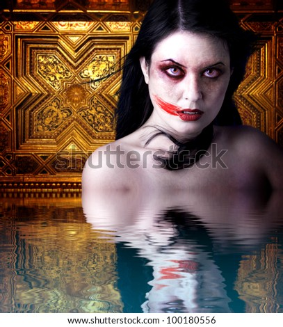 Woman vampire with blood in his mouth. Gothic Image halloween over gold background  in the water reflection - stock photo