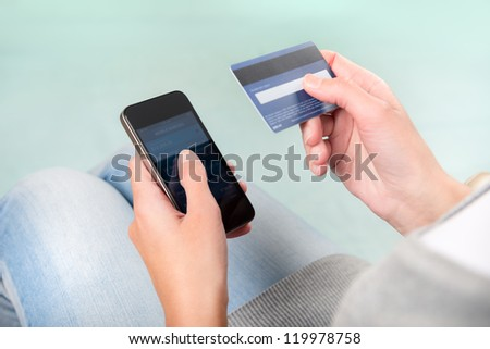 Woman verifies account balance on smartphone with mobile banking application.