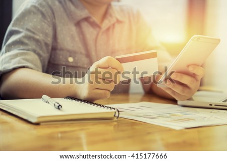Woman verifies account balance on smartphone with mobile banking application.Online payment,Women's hands holding a credit card and using smart phone for online shopping,selective focus,vintage color - stock photo