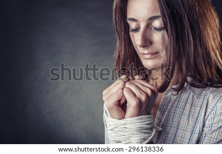 Woman victim of domestic violence and abuse. Young woman on a dark background with their hands tied - stock photo