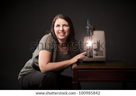 Woman Viewing Old Movies on 8mm Film Projector - stock photo