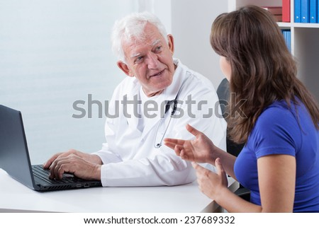Woman visiting experienced physician in his office - stock photo