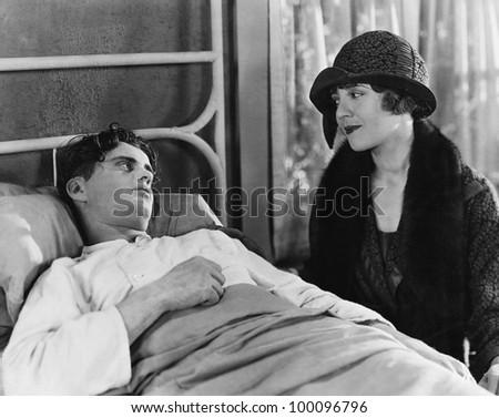 Woman visiting sick man - stock photo