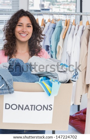 Woman volunteer smiling and holding donation box - stock photo
