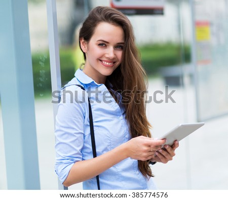 Woman waiting at bus stop  - stock photo
