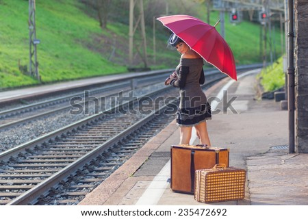 Woman waiting at the railway station with umbrella - stock photo