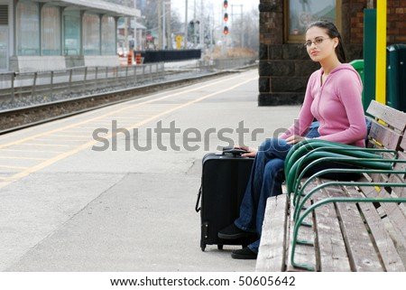 woman waiting at the train station - stock photo
