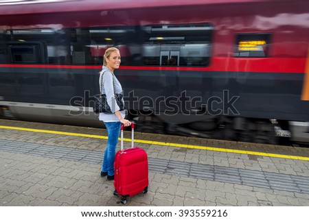 woman waiting for train on railway station - stock photo