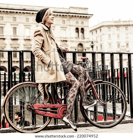 Woman waiting friends for a meeting, while she is sitting on her bicycle. Milan, Italy. - stock photo