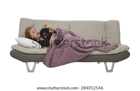 Woman waking up from taking a nap on a sofa against a white background - stock photo