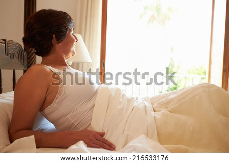 Woman Waking Up In Bed In Morning - stock photo