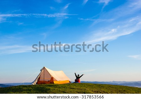 Woman Waking up with the arms up in the air after a night on the top of a Mountain - stock photo