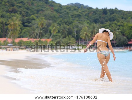 woman walk on a tropical beach - stock photo