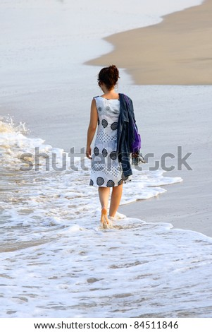 woman walking alone along a deserted beach - stock photo