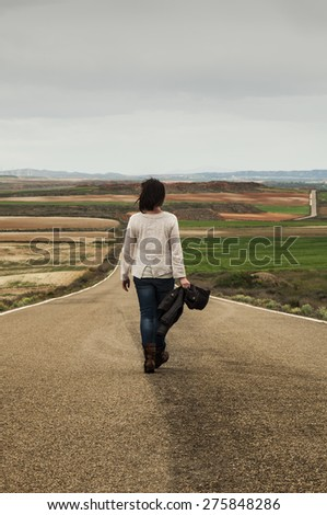 Woman walking alone in a country road