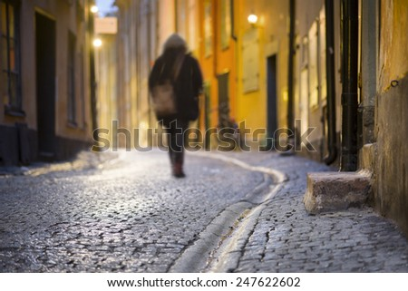 Woman walking along narrow wet street in Stockholm old town at night - stock photo
